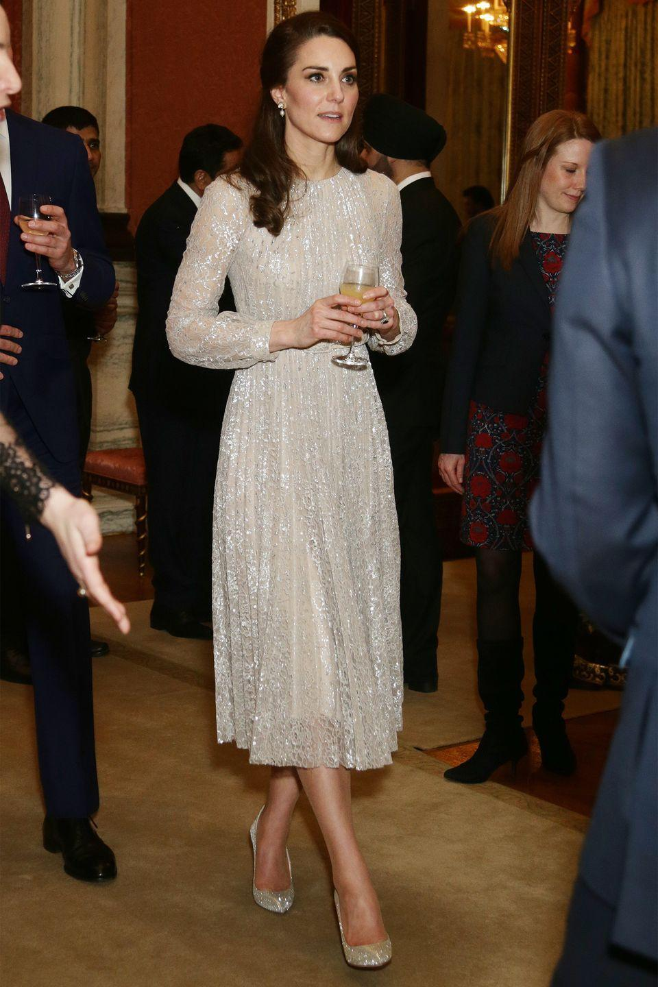 <p>The Duchess wears a shimmering, champagne-colored Erdem dress with dangling pearl earrings and glittery pumps at Buckingham Palace.</p>