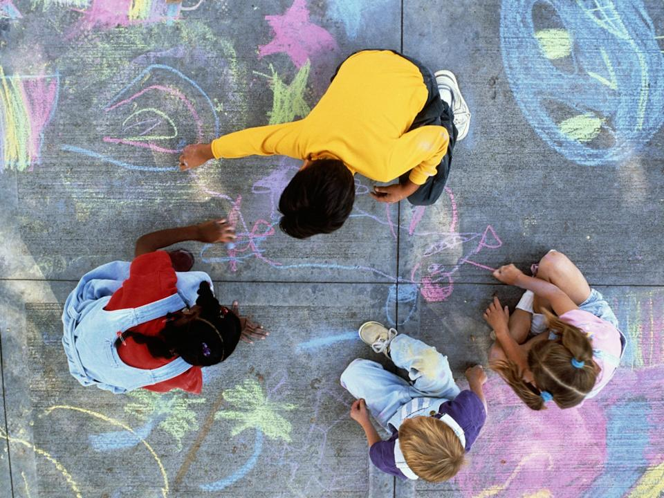 Children drawing with chalk on pavement.