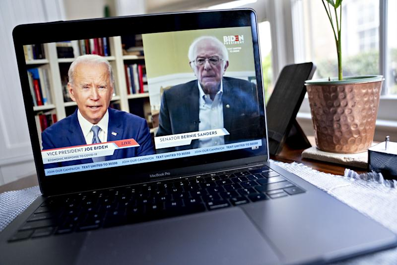 Former Vice President Joe Biden, presumptive Democratic presidential nominee, left, speaks as Senator Bernie Sanders, an Independent from Vermont, right, listens during a virtual event seen on an Apple Inc. laptop computer in Arlington, Virginia, U.S., on Monday, April 13, 2020. Sanders endorsed Biden during the joint livestream saying that Americans of all political affiliations should back the former vice president. Photographer: Andrew Harrer/Bloomberg