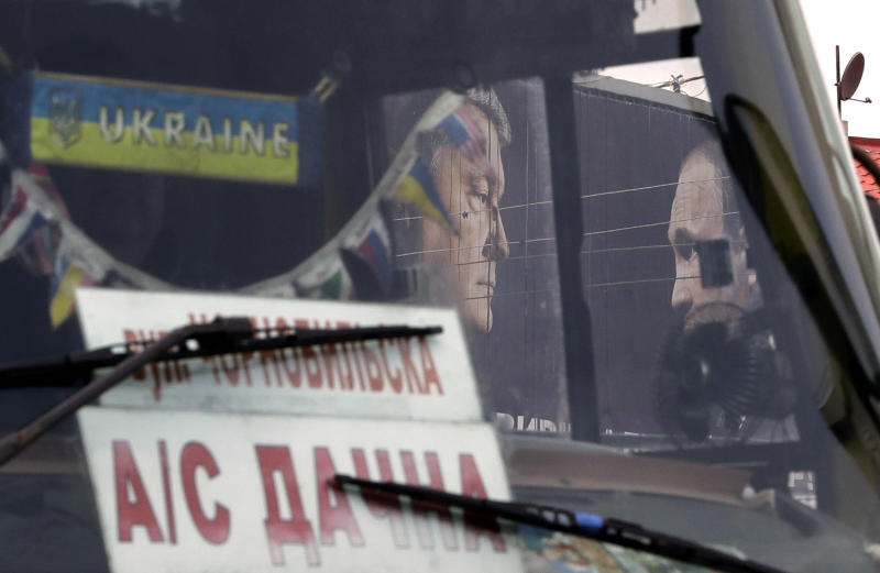 A bus drives past a billboard depicting Ukraine's President Petro Poroshenko and Russian President Vladimir Putin looking at each other in Kiev, Ukraine, Wednesday, April 17, 2019. The second round of presidential vote in Ukraine will take place on April 21. (AP Photo/Sergei Grits)