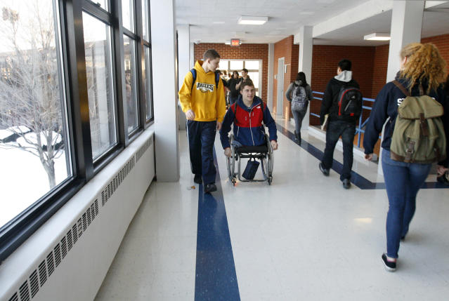 "Brody Roybal, 15, wheels down a hallway with his friend Nick Fredrickson at West Leyden High School in Northlake, Ill. on Tuesday, Feb. 11, 2014. His father, Robert says, in many ways he's ""just another average teenager,"" - one, he adds, ""who's lucky enough to go to the Olympics."" (AP Photo/Martha Irvine)"