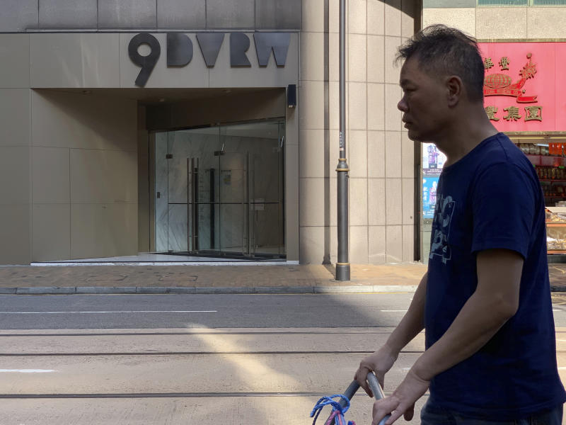 """A worker walks past a building listed as the address of China Innovation Investment Limited in Hong Kong, Saturday, Nov. 23, 2019. Australia's Treasurer on Saturday labeled detailed accusations of China infiltrating and disrupting democratic systems in Australia, Hong Kong and Taiwan as """"very disturbing"""". A Chinese defector revealed he was part of the Hong Kong-based investment firm, which was a front for the Chinese government to conduct political and economic espionage in Hong Kong, including infiltrating universities and directing bashings and cyber attacks against dissidents. (AP Photo/Ng Han Guan)"""