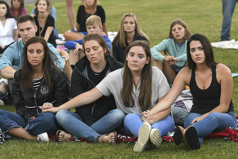 People hold hands during a prayer vigil for the victims of the helicopter accident Thursday, July 11, 2019  at the Paul Cline Memorial Sports Complex in Beckley, W.Va.  Chris Cline, his daughter Kameron Cline, Beckley native Delaney Wykle and four others were killed last week when their helicopter crashed after taking off from a remote private island in the Bahamas.   (Rick Barbero/The Register-Herald via AP)