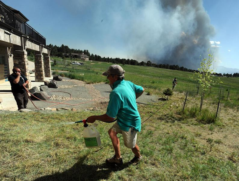 Lynd Fitzgerald sprays fire retardant around a house while a fire burns out of control in the background north of Shoup Road and East of Highway 83 in Colorado Springs, Colo. on Tuesday afternoon, June 11, 2013. The Black Forest Fire was one of at least three significant wildfires burning in Colorado amid gusty winds and record-breaking hot, dry weather. (AP Photo/The Colorado Springs Gazette, Christian Murdock) MAGS OUT