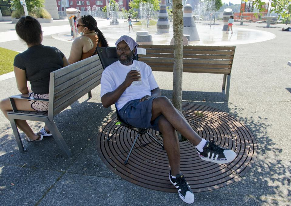 Melvin O'Brien waits in the shade in Yesler Terrace Park while his children play in the spray park during a heat wave hitting the Pacific Northwest, Sunday, June 27, 2021, in Seattle. Yesterday set a record high for the day with more record highs expected today and Monday. (AP Photo/John Froschauer)