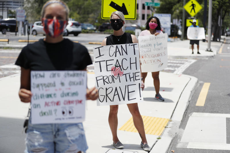 TAMPA, FL - JULY 16: Middle school teacher Brittany Myers, (C) stands in protest in front of the Hillsborough County Schools District Office on July 16, 2020 in Tampa, Florida. Teachers and administrators from Hillsborough County Schools rallied against the reopening of schools due to health and safety concerns amid the COVID-19 pandemic. (Photo by Octavio Jones/Getty Images)