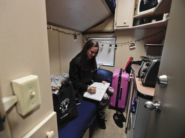 <p>Ringling Bros. clown Beth Walters writes in a journal in her living quarters on the circus' train before heading off to the arena to perform in a show, Thursday, May 4, 2017, in Providence, R.I. Walters had taken down most of the photos and decorations in her room to prepare to move out and head home after the red unit's final performance. (Photo: Julie Jacobson/AP) </p>