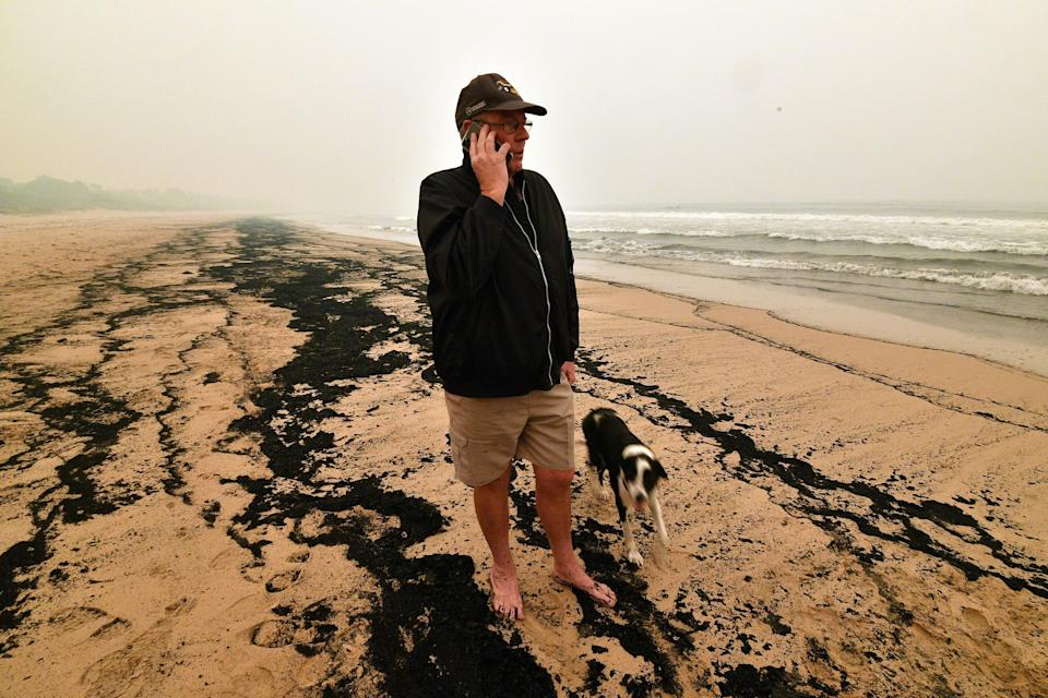 Resident Dave Iredale talks on his phone while standing amongst ash from bushfires washed up on a beach in Merimbula.