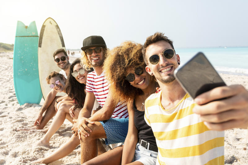 Friends sitting on the beach, having fun, taking selfies
