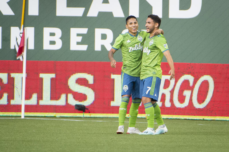 Aug 23, 2019; Portland, OR, USA; Seattle Sounders midfielder Cristian Roldan (7) celebrates with forward Raul Ruidiaz (9) after scoring a goal during the first half against the Portland Timbers at Providence Park. Mandatory Credit: Troy Wayrynen-USA TODAY Sports