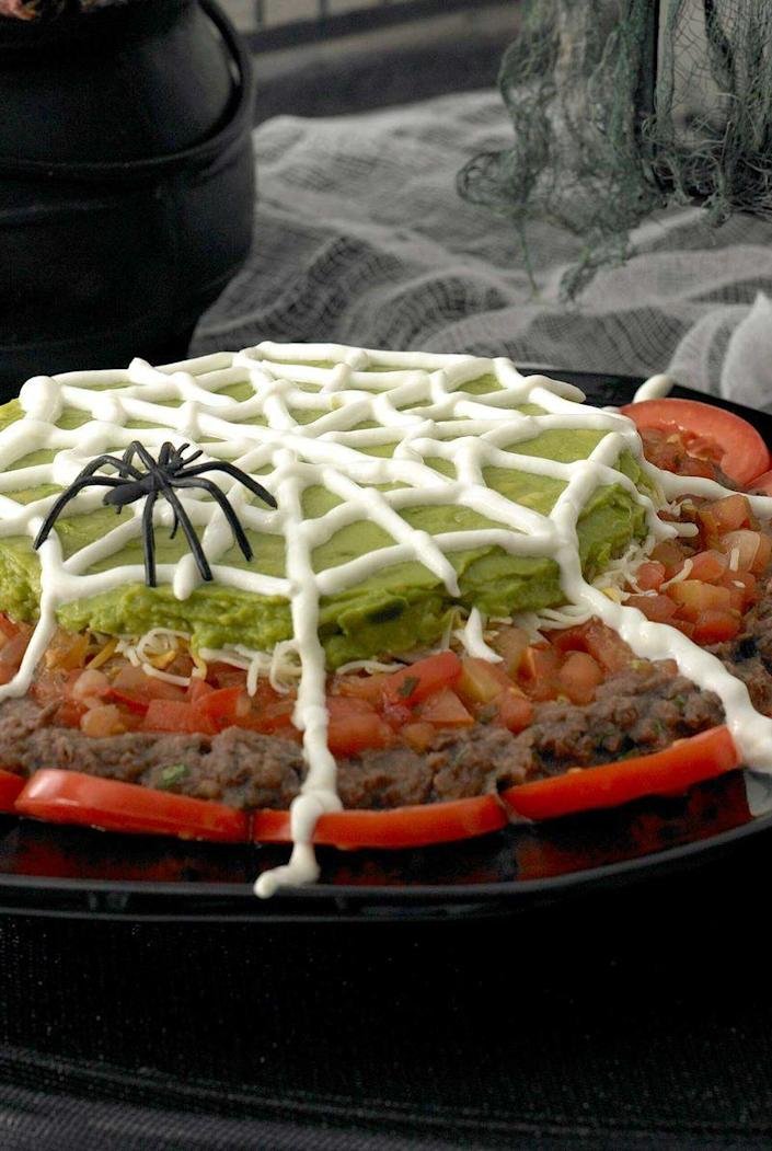 """<p>It's a party classic: nacho bean dip, only with a creepy-crawly twist. Make it up to four hours ahead of time and pull it from the fridge when you're ready to party.</p><p><em><strong><a href=""""https://www.womansday.com/food-recipes/food-drinks/recipes/a9948/spiderweb-nacho-spread-recipe-121386/"""" rel=""""nofollow noopener"""" target=""""_blank"""" data-ylk=""""slk:Get the Halloween Nachos recipe"""" class=""""link rapid-noclick-resp"""">Get the Halloween Nachos recipe</a>.</strong></em><br></p>"""
