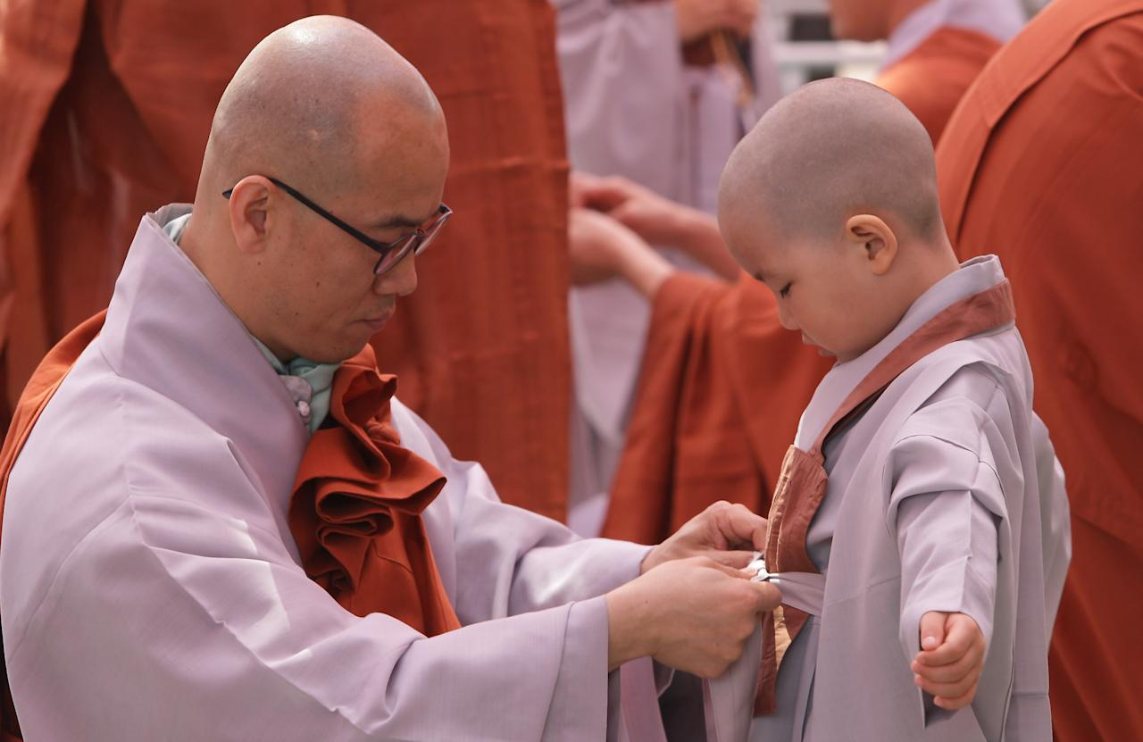 SEOUL, SOUTH KOREA - MAY 03:  Children are dressed in robes by monks during the 'Children Becoming Buddhist Monks' ceremony forthcoming buddha's birthday at a Chogye temple on May 3, 2013 in Seoul, South Korea. The children will stay at the temple to learn about Buddhism for 14 days. Buddha was born approximately 2,557 years ago, and although the exact date is unknown, Buddha's official birthday is celebrated on the full moon in May in South Korea, which is on May 17 this year.  (Photo by Chung Sung-Jun/Getty Images)