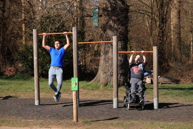 People exercise on outdoor equipment at Stoke Park in Guildford