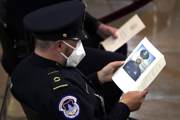 "A U.S. Capitol Police officer looks at the program for U.S. Capitol Police officer William ""Billy"" Evans as he lies in honor during a ceremony at the Capitol in Washington, Tuesday, April 13, 2021. (Amr Alfiky/The New York Times via AP, Pool)"