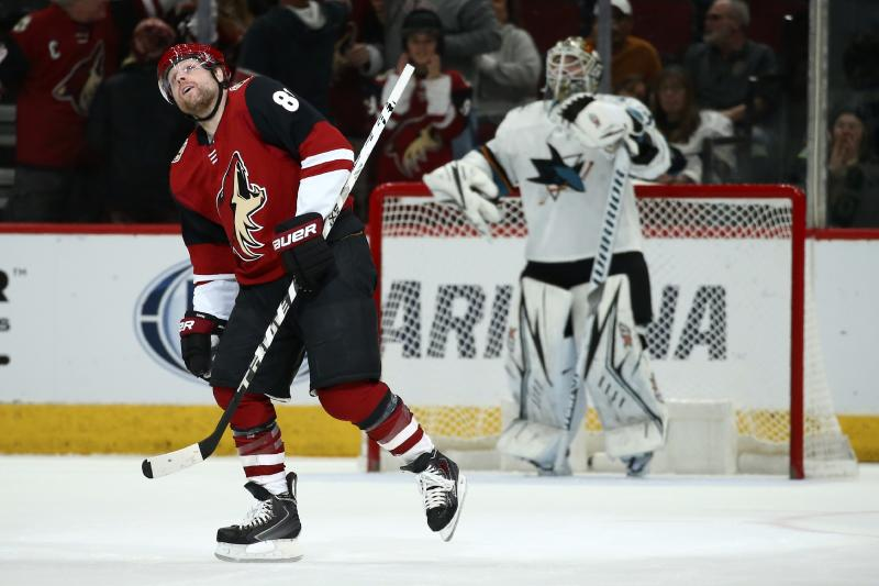 Arizona Coyotes right wing Phil Kessel, left, watches his goal against San Jose Sharks goaltender Aaron Dell, right, on the scoreboard screen during the first period of an NHL hockey game Tuesday, Jan. 14, 2020, in Glendale, Ariz. (AP Photo/Ross D. Franklin)