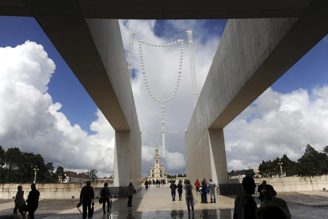 "<p>Pilgrims walk by a 26 metre tall giant glow-in-the-dark rosary, titled ""Suspension"" by the Portuguese artist Joana Vasconcelos, above the entrance of Basilica of the Holy Trinity, in Fatima, Portugal, May 11, 2017. Pope Francis is visiting the Fatima shrine on May 12 and 13 to canonize two Portuguese shepherd children whose ""visions"" of the Virgin Mary 100 years ago turned the sleepy farming town of Fatima into a major Catholic pilgrimage site. (Photo: Paulo Duarte/AP) </p>"