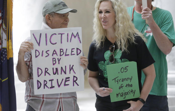 FILE - In this March 17, 2017, file photo, Ed Staley, left, and Tali Bruce, right, attend a rally concerning the DUI threshold at the Utah state Capitol in Salt Lake City. The United States' lowest DUI threshold takes effect this weekend in Utah. Lawmakers in the state approved the 0.05 percent blood-alcohol limit in 2017, and Gov. Gary Herbert signed it into law. The change goes into effect Saturday, Dec. 29, 2018. (AP Photo/Rick Bowmer, File)