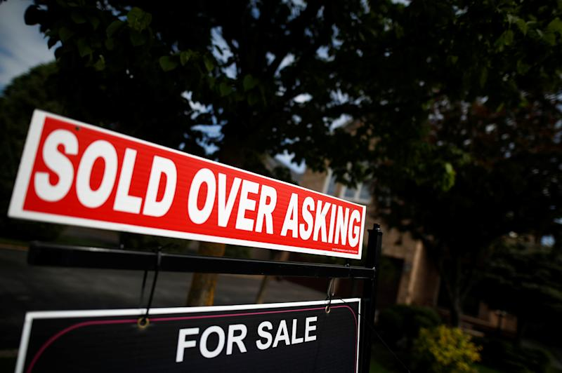 "A real estate sign that reads ""For Sale"" and ""Sold Above Asking"" stands in front of housing in Vaughan, a suburb in Toronto, Canada, May 24, 2017. REUTERS/Mark Blinch"