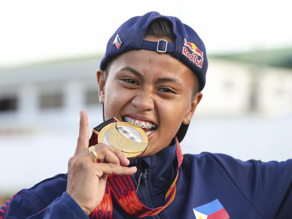 Gold medalist Philippines' Margielyn Didal poses during the awarding ceremony of the street event finals of skateboarding at the 30th South East Asian Games in Tagaytay City, Cavite Province, Philippines, on Saturday, December 7, 2019. (AP Photo/Jijo de Guzman)