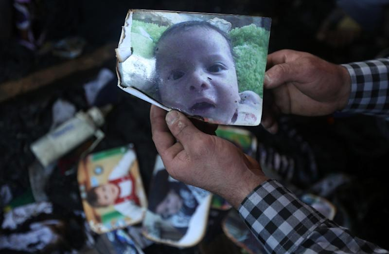 A man holds a picture of Palestinian toddler Ali Dawabsha who died when the family home was set on fire in the West Bank village of Duma in July 2015
