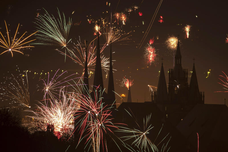 Fireworks light the sky above the St. Severi's Church, left, and the Mariendom (Cathedral of Mary), right, during New Year's celebrations in Erfurt, central Germany, Wednesday, Jan. 1, 2020. (AP Photo/Jens Meyer)