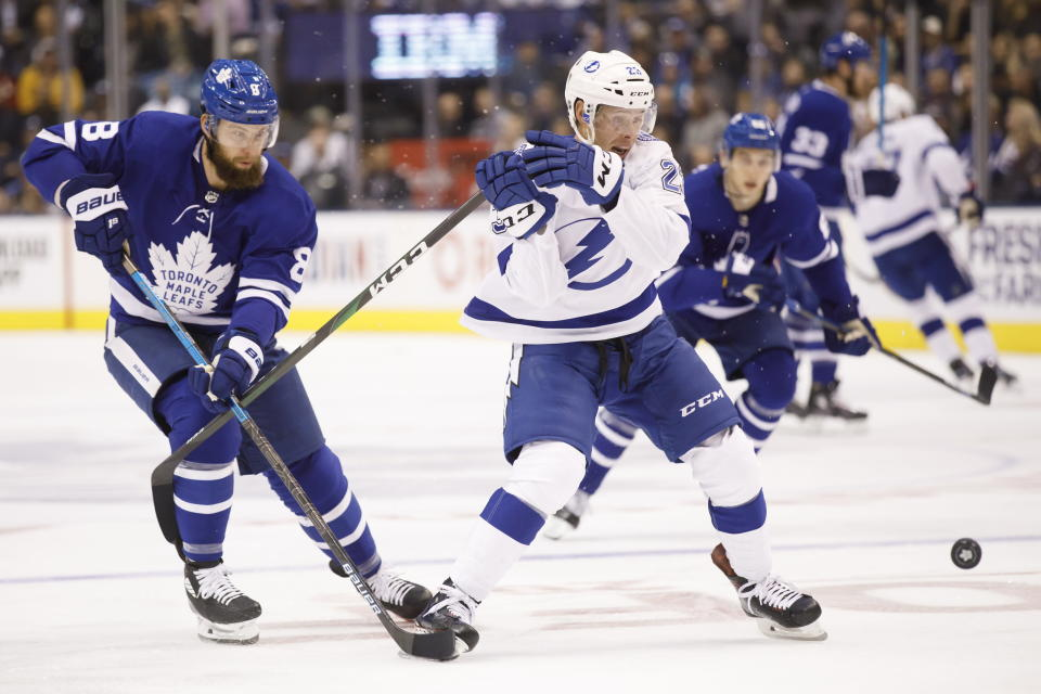 Tampa Bay Lightning center Carter Verhaeghe (23) and Toronto Maple Leafs defenseman Jake Muzzin (8) vie for the puck during the first period of an NHL hockey game Thursday, Oct. 10, 2019, in Toronto. (Cole Burston/The Canadian Press via AP)