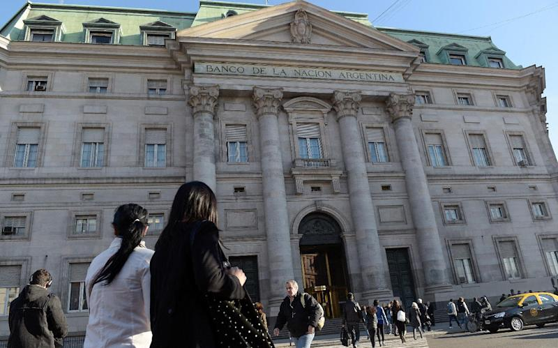 People walk by the Bank of the Nation headquarters in front of Plaza de Mayo square in Buenos Aires on July 30, 2014 (AFP Photo/Daniel Garcia)