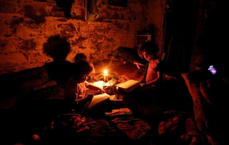 Palestinian children do their homework during a power cut in Gaza City in September 2017 (AFP Photo/MAHMUD HAMS)