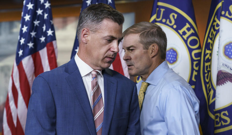 Rep. Jim Banks, R-Ind., left, and Rep. Jim Jordan, R-Ohio, exchange places at the podium during a news conference on Capitol Hill Wednesday. (AP Photo/J. Scott Applewhite)