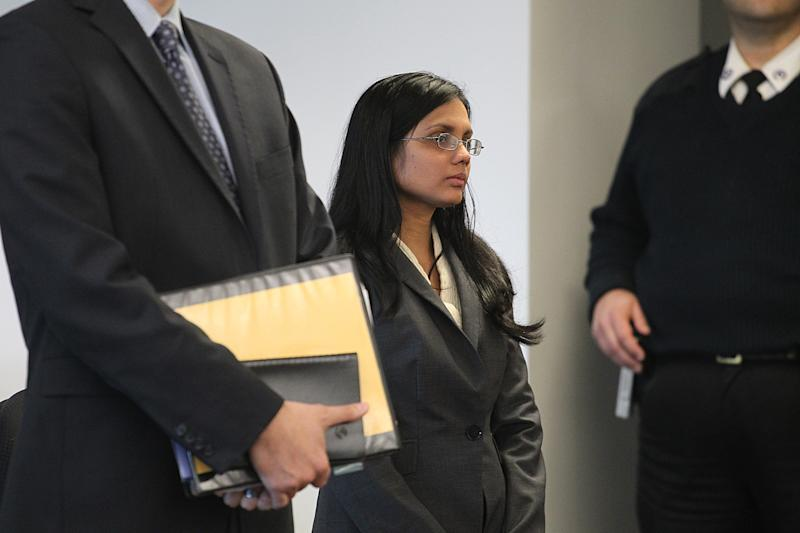 Former state lab chemist Annie Dookhan, center, stands in Middlesex Superior Court for arraignment on Wednesday, Jan. 9, 2013, with her attorney Nick Gordon, left, in Woburn, Mass. Dookhan pleaded not guilty to three counts of obstruction of justice. She is charged in connection with altering drug evidence during the testing process and obstructing justice. Prosecutors allege Dookhan fabricated test results and tampered with drug evidence while testing substances in criminal cases. (AP Photo/The Boston Globe, Suzanne Kreiter, Pool)