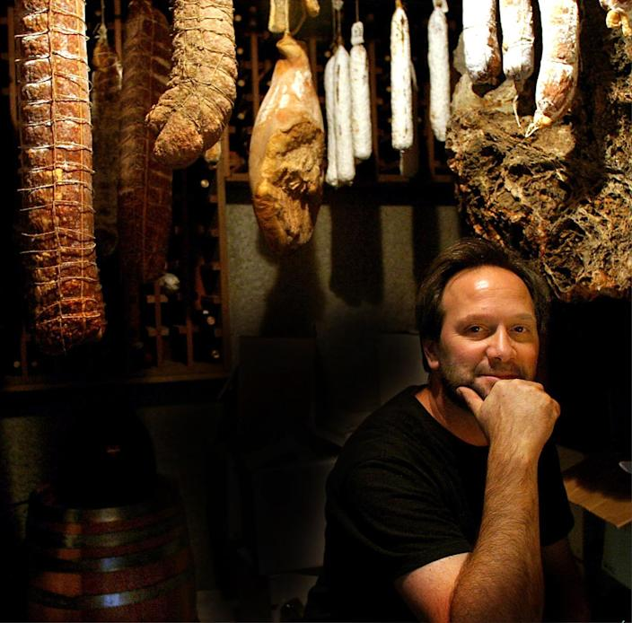 A man with his chin resting in his hand sits in the cellar at his home.