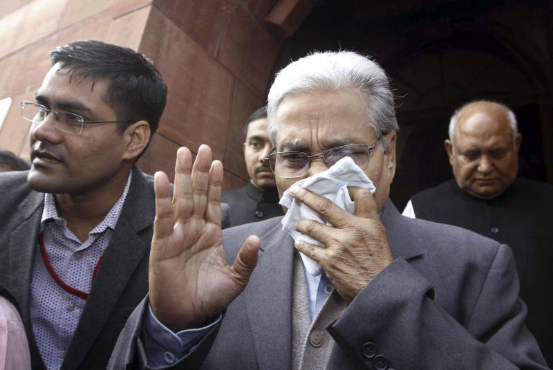 An unidentified member of India's Parliament covers his face with a handkerchief after being affected by pepper spray gas in New Delhi, India, Thursday, Feb. 13, 2014. Congress party lawmaker L. Rajagopal from Andhra Pradesh sprayed pepper spray inside India's Parliament on Thursday from the main speaking zone, creating chaos that left his colleagues coughing and crying as they were ushered from the hall, in a protest over a long-contentious proposal to create a new southern state of Telangana from the existing Andhra Pradesh state. (AP Photo)