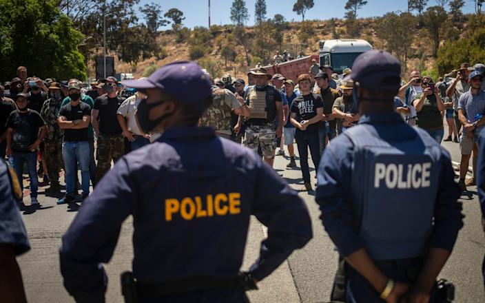 Farmers block the main road as they stand off against Economic Freedom Fighters (EFF) during the bail application for two men accused of murdering young farm manager Brendin Horner - Shutterstock