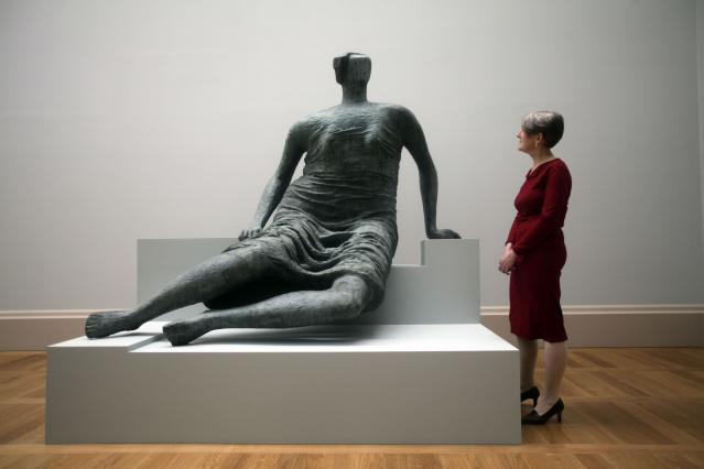 LONDON, UNITED KINGDOM - MAY 13: Penelope Curtis, Director of Tate Britain, stands next to the Henry Moore sculpture Draped Seated Figure which is on display at the Walk through British Art exhibition at Tate Britain on May 13, 2013 in London, England. Visitors will experience a completely new presentation of the world's greatest collection of British art, the national collection of British art will be displayed in a continuous and purely chronological display from the 1500s to the present day. (Photo by Warrick Page/Getty Images)