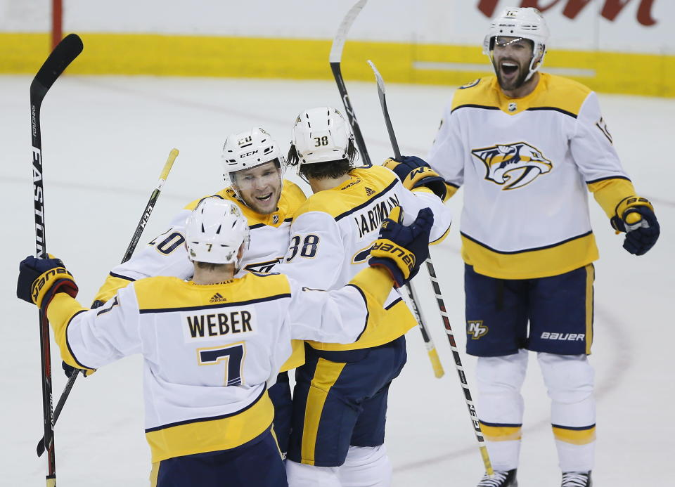 Nashville Predators' Yannick Weber (7), Miikka Salomaki (20), Mike Fisher (12) and Ryan Hartman (38) celebrate Hartman's goal against the Winnipeg Jets during the first period of Game 4 of an NHL hockey second-round playoff series in Winnipeg, Manitoba, Thursday, May 3, 2018. (John Woods/The Canadian Press via AP)