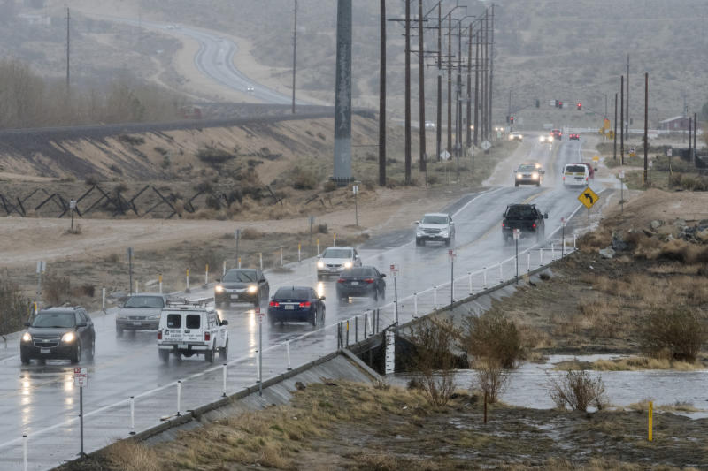 Traffic drives over Rock Springs Road as rain water begins filling the Mojave River in Hesperia CA on Thursday January 17, 2019. The Mojave River flows underground the majority of the year. (James Quigg/The Daily Press via AP)
