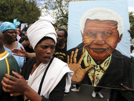 A mourner sings next to a poster former South African President Nelson Mandela outside his residence in Johannesburg December 6, 2013. REUTERS/Siphiwe Sibeko
