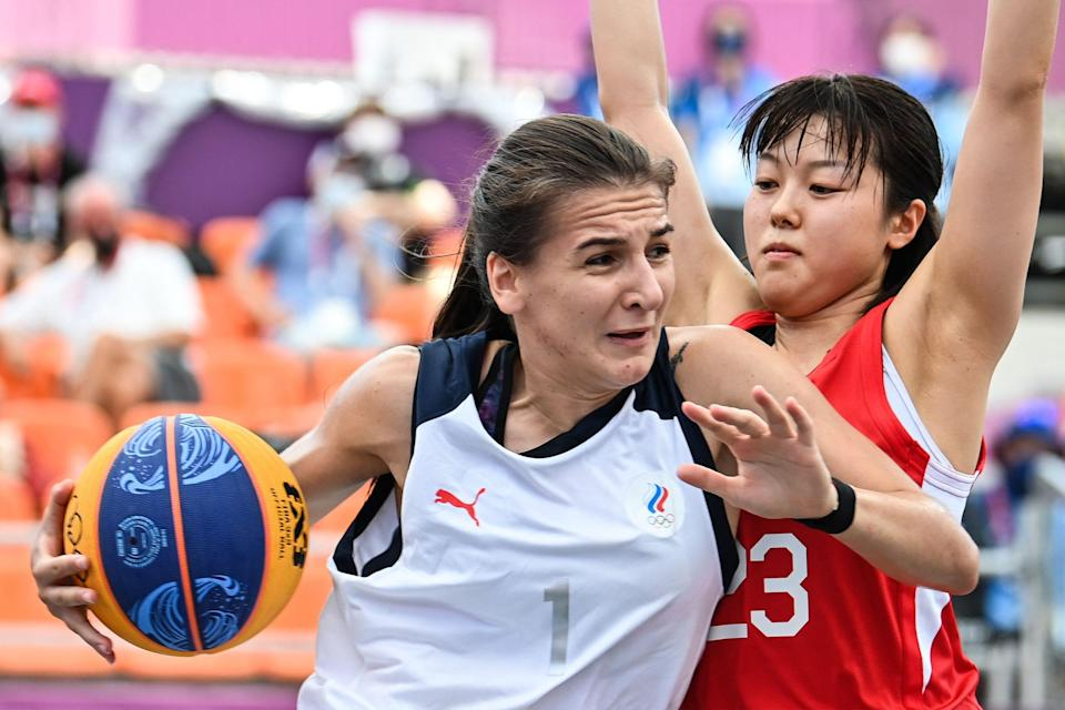 Russia's Yulia Kozik (L) and Japan's Mai Yamamoto fight for the ball during the women's first round 3x3 basketball match.