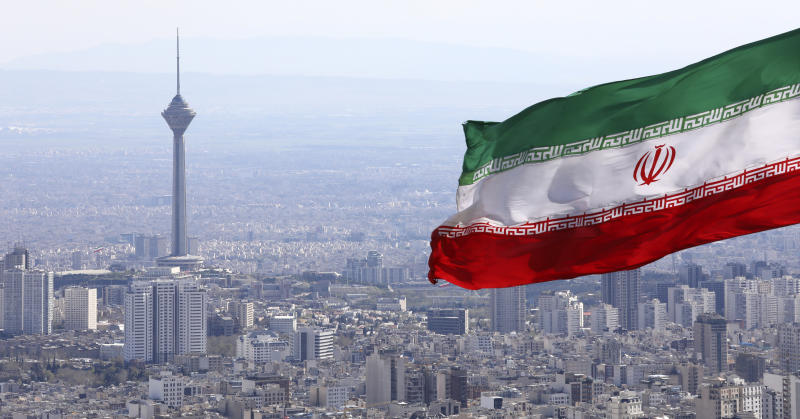 Iran's national flag waves as Milad telecommunications tower and buildings are seen in Tehran, Iran, Tuesday, March 31, 2020. In recent days, Iran which is battling the worst new coronavirus outbreak in the region, has ordered the closure of nonessential businesses and banned intercity travels aimed at preventing the virus' spread.   (AP Photo/Vahid Salemi)