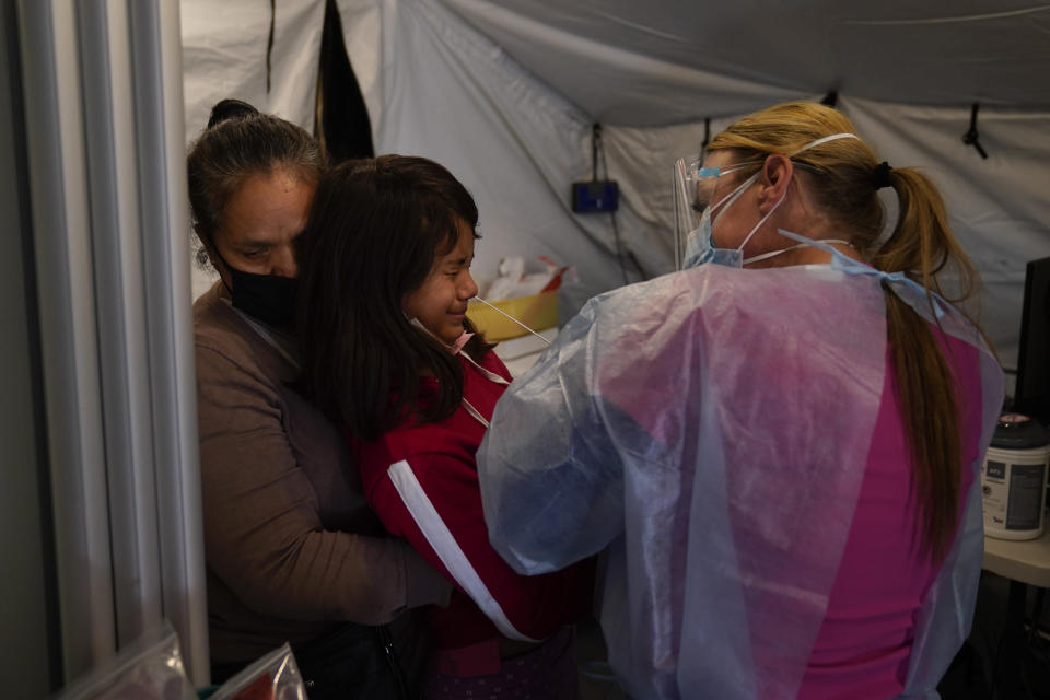 Held by grandmother Maria Ortiz, 11-year-old Star Estrada, center, grimaces as registered nurse Angela Coomds collects a nasal swab sample from her in a COVID-19 triage tent at Providence Holy Cross Medical Center in the Mission Hills section of Los Angeles, Tuesday, Dec. 22, 2020. (AP Photo/Jae C. Hong)