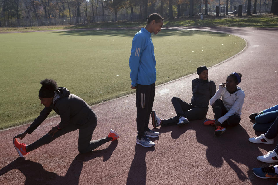A group of Ethiopian runners stretches and talks before a short workout at Van Cortlandt Park in the Bronx borough of New York, Tuesday, Nov. 26, 2019. Girma Bekele Gebre stunned the elite field at the New York City Marathon by finishing third as a nonelite entrant in November. It was a life-changing performance for the Ethiopian runner, and one made possible because of his involvement with the West Side Runners' Club. Team President Bill Staab has spent four decades helping immigrant runners acquire visas and gain entry to U.S. races, spending nearly $1 million of his own money to cover fees. Bekele Gebre is his greatest success, but not nearly the only runner he's helped. (AP Photo/Seth Wenig)