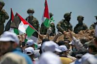 Demonstrators wave Palestinian flags while Israeli forces stand on guard during a protest against Jewish settlements and Israel's planned annexation of parts of the Israeli-occupied West Bank, near the West Bank city of Nablus on July 10 (AFP Photo/ABBAS MOMANI)