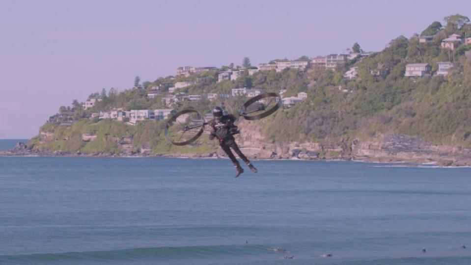 A pilot using an electric jetpack to fly above the beach in Australia.