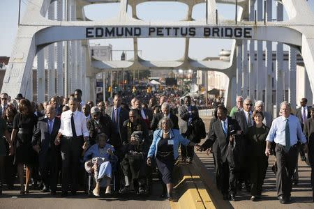 U.S. President Barack Obama (3rd L) participates in a march across the Edmund Pettus Bridge in Selma, Alabama, March 7, 2015. Also pictured are first lady Michelle Obama (L), U.S. Representative John Lewis (D-GA) (2nd L), former first lady Laura Bush (2nd R) and former president George W. Bush (R). REUTERS/Jonathan Ernst