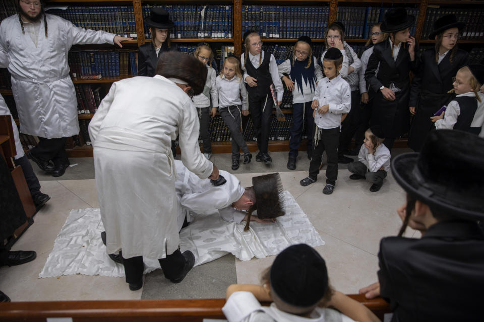 An ultra-Orthodox Jewish man whips a member of his Hasidic dynasty with a leather strap as a symbolic punishment for his sins last year's, during the traditional Malkot (whipping in Hebrew) ceremony, ahead of Yom Kippur that begins at sunset, in the city of Beit Shemesh, near Jerusalem, Wednesday, Sept. 15, 2021. Yom Kippur is Judaism's day of atonement, when devout Jews ask God to forgive them for their transgressions and refrain from eating and drinking, attending intense prayer services in synagogues. (AP Photo/Oded Balilty)