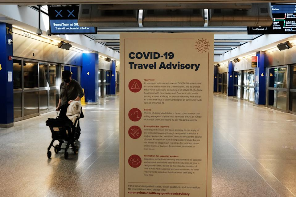 NEW YORK, NEW YORK - JANUARY 25: Covid-19 information is displayed at an international terminal at John F. Kennedy Airport (JFK) on January 25, 2021 in New York City. In an effort to further control Covid-19 transmission, President Joe Biden plans to sign restrictions on travel to the United States. The ban will prohibit travelers from the United Kingdom, Ireland and 26 countries in Europe that allow travel across open borders, called the Schengen Area. The new measures will also block entry to travelers from Brazil and South Africa. (Photo by Spencer Platt/Getty Images)