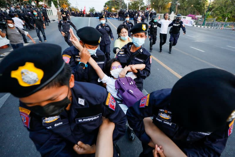 A pro-democracy protester flashes the three-finger salute while she is detained by police officers in front of the Government House during a rally in Bangkok