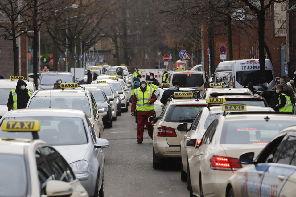People as the arrive and departure with taxies at the vaccination center against the COVID-19 disease in the district Treptow in Berlin, Germany, Thursday, Jan. 28, 2021. (AP Photo/Markus Schreiber)