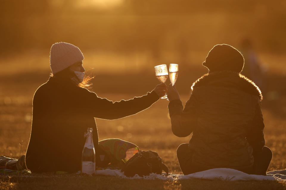 Women toast during a sunset at Cruzeiro Square in Brasilia, Brazil, Friday, July 31, 2020. People gathered in the late afternoon as authorities eased the restrictions related to the new coronavirus, despite that Brazil's official COVID-19 death toll is the second highest in the world after the United States. (AP Photo/Eraldo Peres)