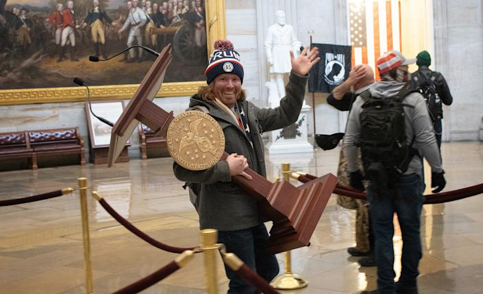 Adam Johnson carries the lectern of U.S. Speaker of the House Nancy Pelosi through the Roturnda of the U.S. Capitol Building after a pro-Trump mob stormed the building on January 06, 2021 in Washington, DC. (Win McNamee/Getty Images)